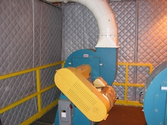 An industrial blower located in a manufacturing facility enclosued in soundproofing material.